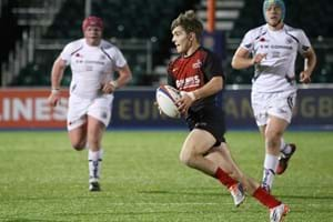 A Hartpury student running with the ball during a rugby game