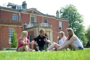 students sitting on the grass in front of Hartpury house
