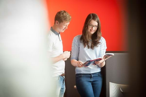 two students in the college learning centre looking at a book