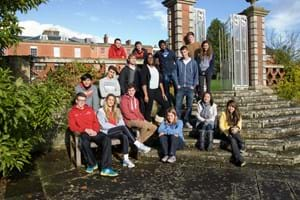 A group of Hartpury students standing in front of Hartpury house