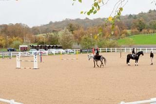 students riding horses in an outdoor arena at Hartpury