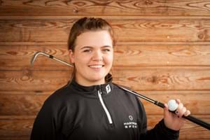 student holding golf club and golf ball
